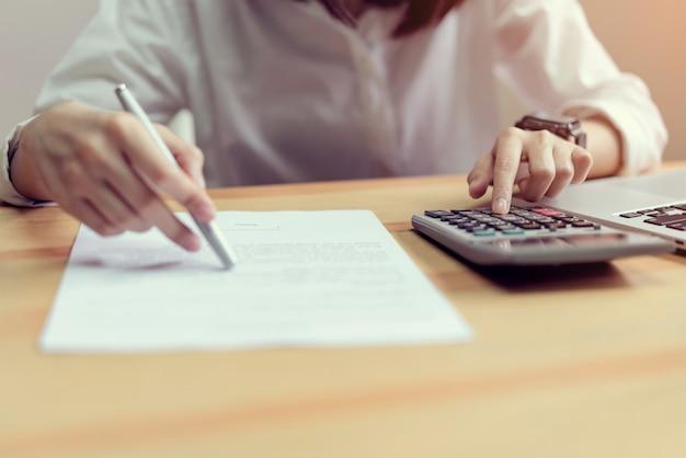 Женщина проверяет документы соглашения и использует калькулятор на столе в офисе
