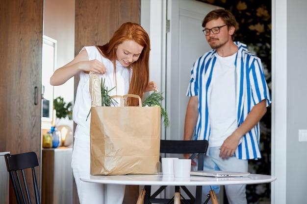 女性は夫が持ってきた購入品をチェックします