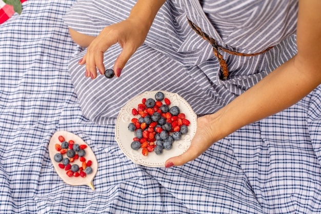Woman in checkered stylish dress take berry from berries plate. outdoor picnic