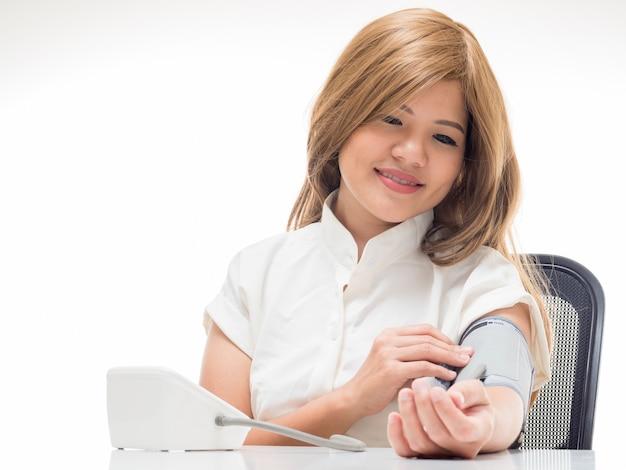 白い背景の上の血圧をチェックする女性