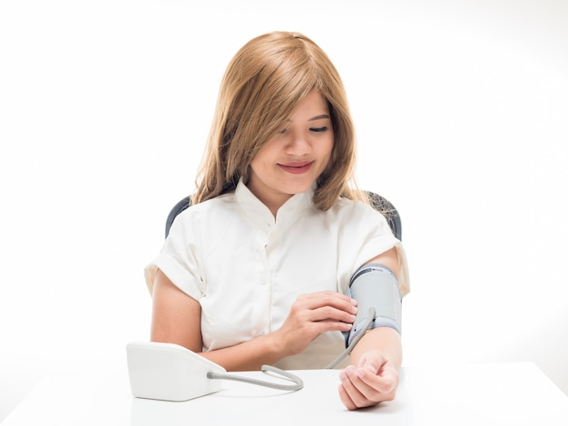 Woman checking blood pressure on white background