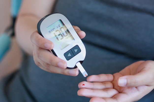 Woman checking blood sugar level with glucometer