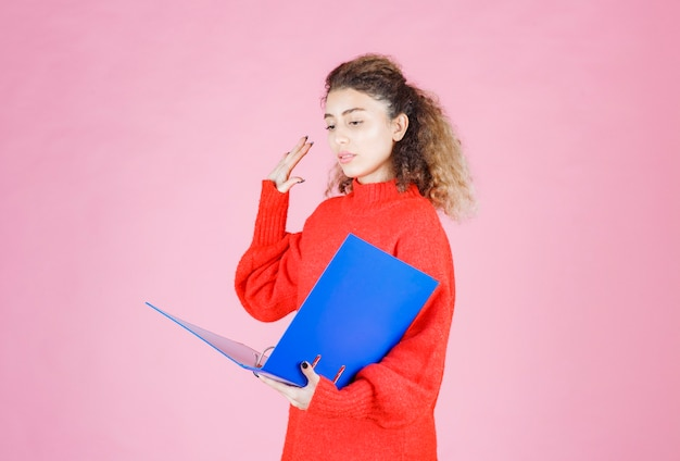 Woman checking the blue folder and raising her hand.
