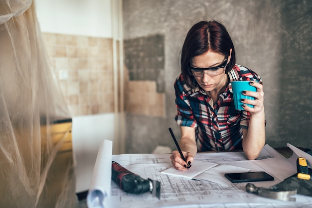 Woman checking blueprint and drinking coffee