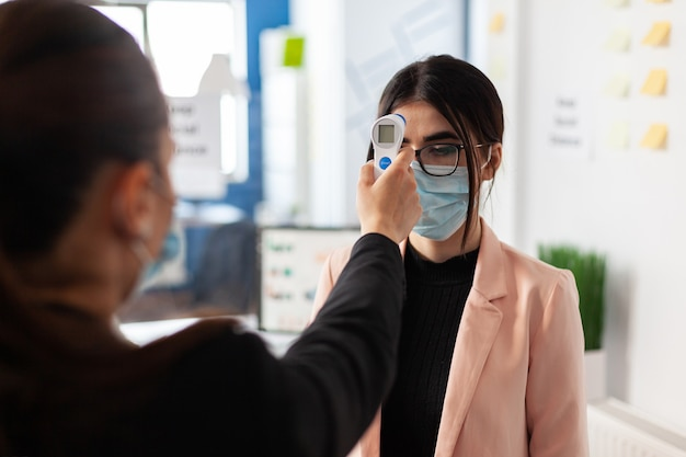 Woman checking colleague temperature using digital thermometer in work office during global pandemic with coronavirus, wearing face mask as safety precaution. new normal virus outbreak.