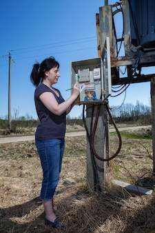 Woman checking electric meter reading, standing near electricity switchgear.