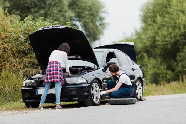Woman checking engine and man changing tire