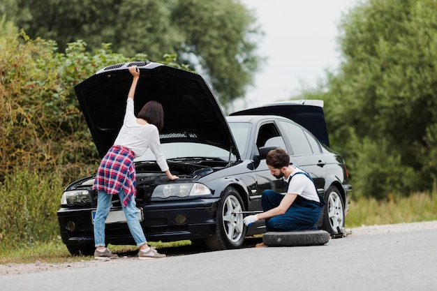 Woman checking engine and man swapping tire