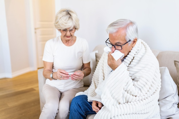 Woman checking fever temperature of senior man sitting on bed