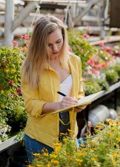 Женщина проверяет потребности повестки дня парниковых