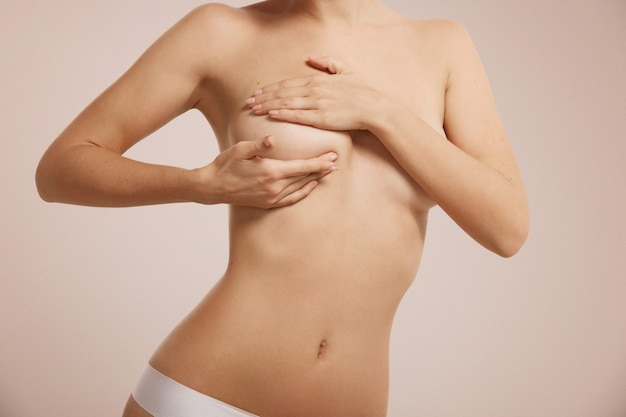 Woman checking her breast for breast cancer