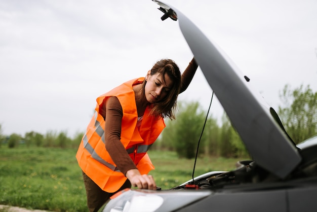 Woman checking her broken car on road.
