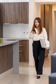 출근하기 위해 집을 나서면서 휴대전화를 확인하는 여성 퇴근하기 위해 집을 나서는 여성