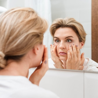 Woman checking her eyes in the mirror