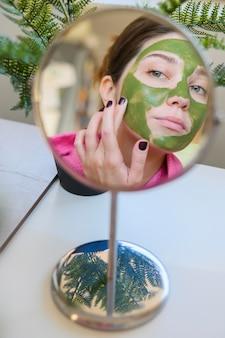 鏡の中の彼女のフェイスマスクをチェックする女性