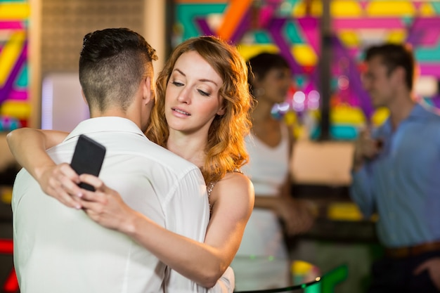 Woman checking her mobile phone while embracing a man