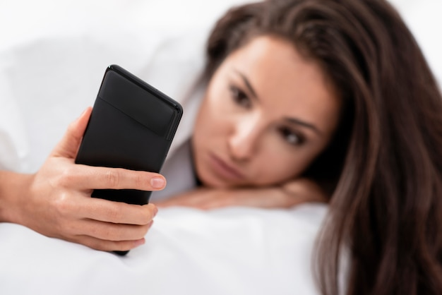 Woman checking her phone after waking up close-up