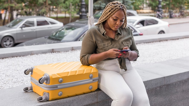 Женщина проверяет свой телефон рядом с ее багажом