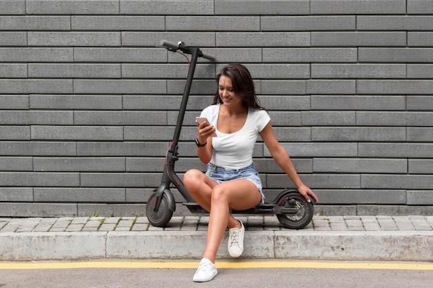 Женщина проверяет свой телефон, сидя на скутере