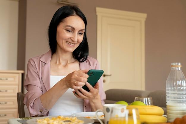 아침 식사를 기다리는 동안 그녀의 전화를 확인하는 여자