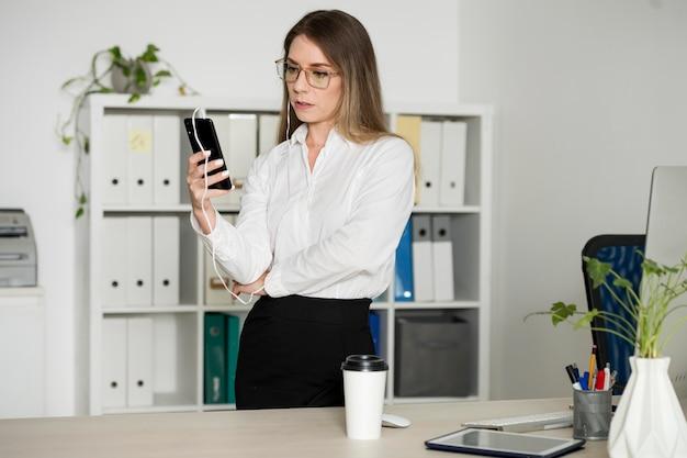 Donna che controlla il telefono al lavoro