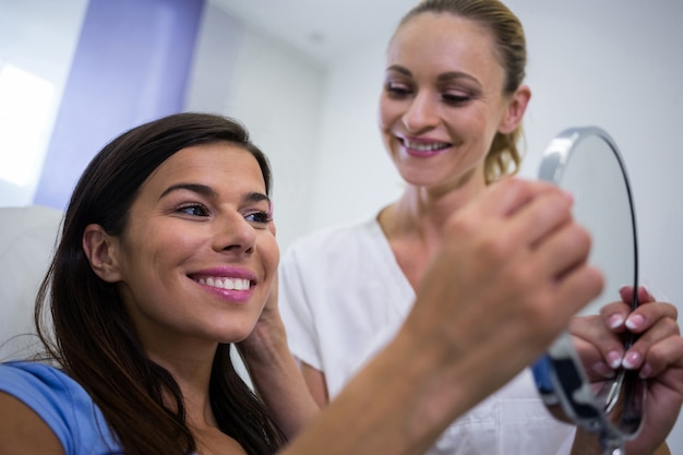 미용 치료를받은 후 거울에 그녀의 피부를 확인하는 여자