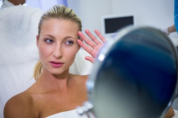 Женщина проверяет свою кожу в зеркале после получения косметического лечения