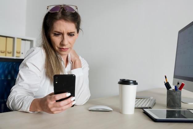 Женщина проверяет свой смартфон на работе
