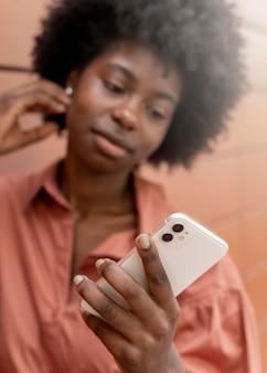 Женщина проверяет свой смартфон на наличие уведомлений