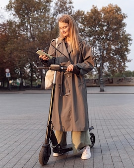 Donna che controlla il suo smartphone mentre su scooter elettrico all'aperto