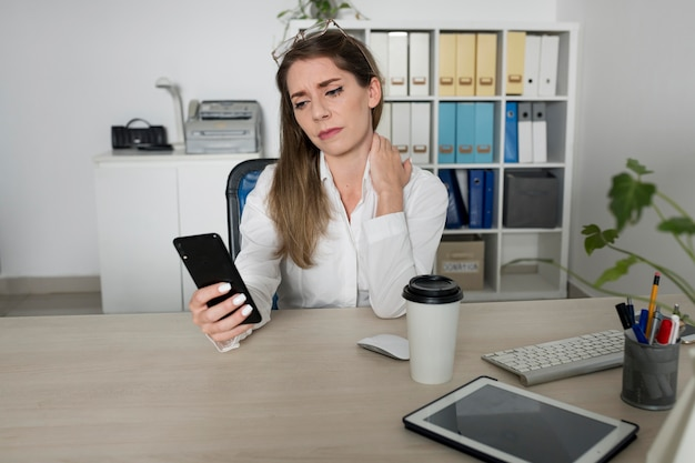 Woman checking her smartphone at work