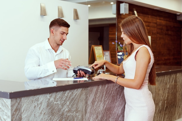 Woman checking in at hotel reception