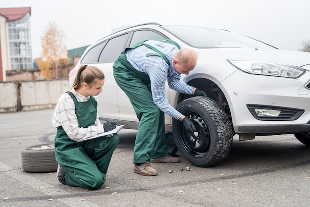 어떻게 작업자가 자동차의 바퀴를 변경하는 방법을 확인하는 여자