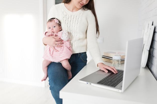 Donna che controlla il computer portatile con il bambino