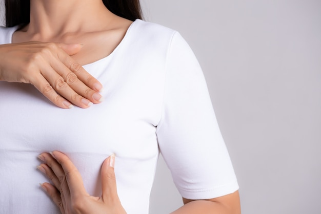 Woman checking lumps on her breast for signs of breast cancer.