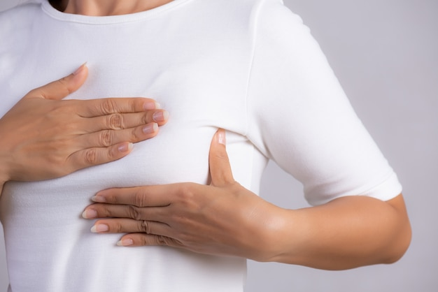 Woman checking lumps on her breast for signs of breast cancer