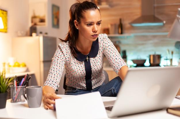 Женщина проверяет заметки в буфере обмена, работая на ноутбуке поздно ночью в домашней кухне, сидя за столом. сотрудник, использующий современные технологии в полночь, выполняет сверхурочную работу по работе, бизнесу, карьере, сети.