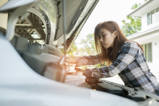 Womanchecking oil level in a car change oil car