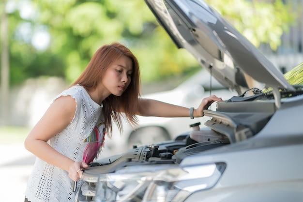 車のオイルレベルをチェックする女性はオイルカーを交換します