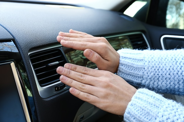 Woman checking operation of air conditioner in car