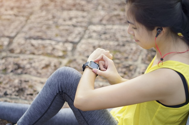 Woman checking progress on smart watch connect listen music to earphone, wearable fitness device.