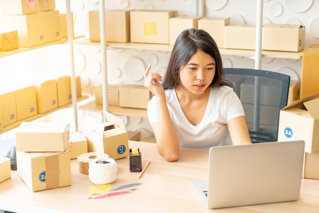 Woman checking purchase order in laptop