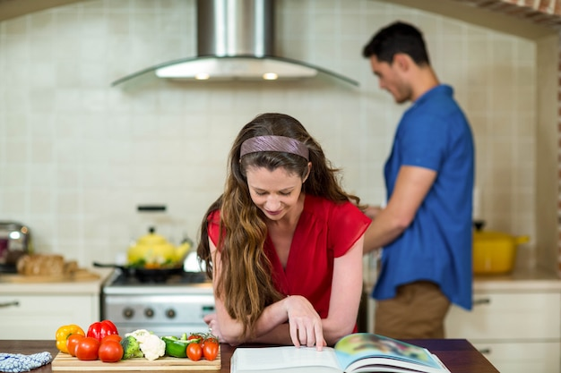 Woman checking the recipe book in kitchen while man cooking on stove in background