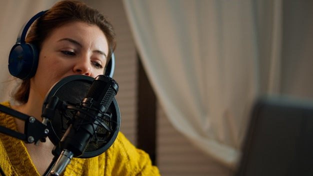 ホームスタジオでライブポッドキャストを録音する前に音をチェックする女性。ストリーミングステーション、メディア機器、ラップトップを備えたビデオオンエアオンライン制作インターネット放送ショーのホストを作る女性司会者、