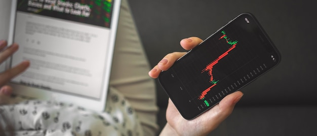 Woman checking stock market price chart on mobile phone while reading the news, banner photo