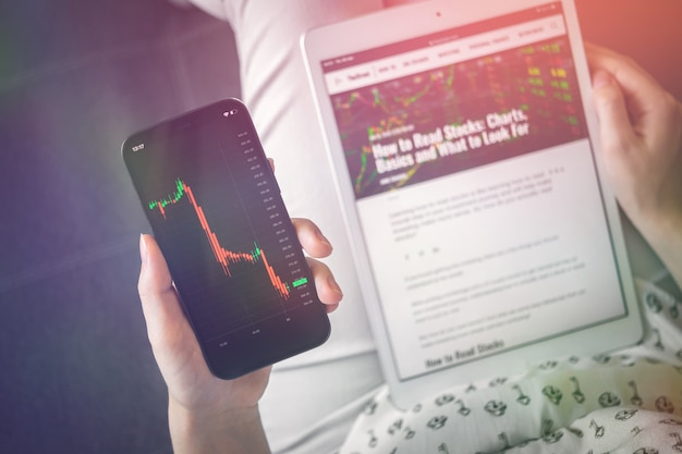 Woman checking stock market price chart on mobile phone while reading the news. price prediction concept background, cryptocurrency future photo