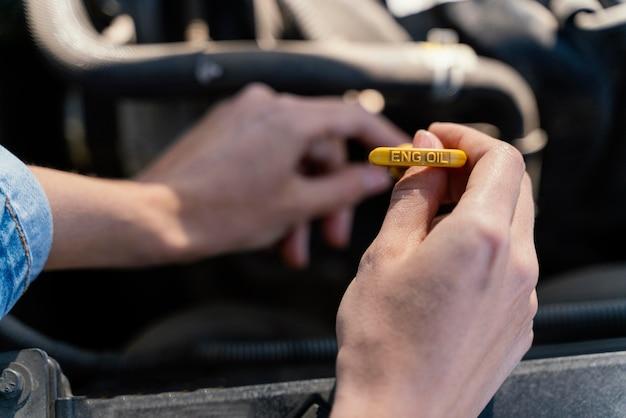 車のオイルをチェックする女性