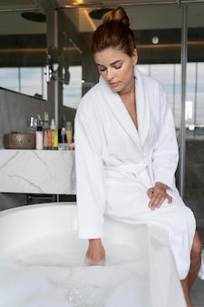 お風呂の水をチェックする女性