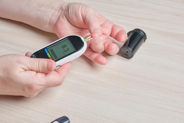 Женщина проверяет уровень сахара в крови глюкометром, капля крови на пальце