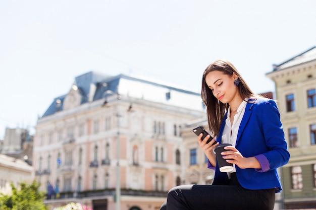 Женщина проверяет свой телефон, сидя с чашкой кофе на улице